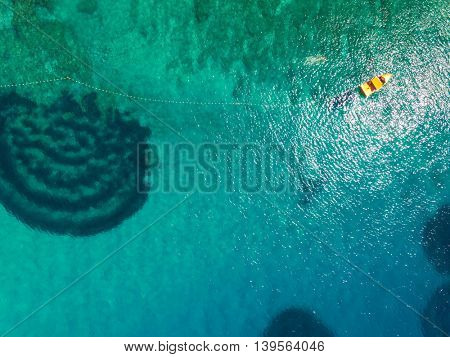 Aerial view of boat attached to net with spiral shape seaweed in Croatia