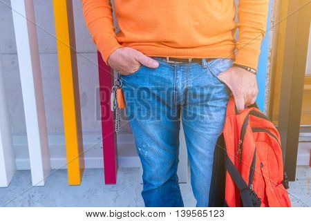 Street fashion. Male outdoor portrait. Man standing near colored building in jeans, orange sweater holding  backpack, detail. Image toned.