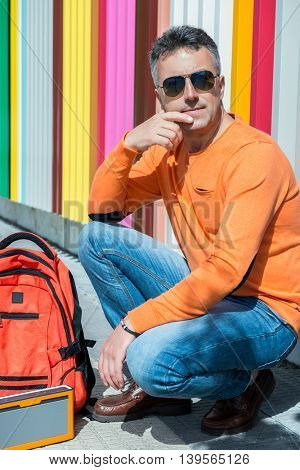 Street fashion. Male outdoor portrait. Man standing near colored building in jeans, orange sweater holding  backpack.