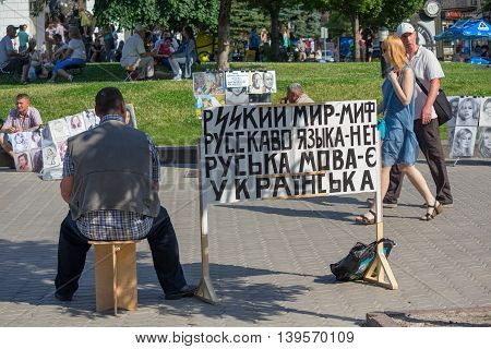 Kiev Ukraine - June 19 2016: Activist sits on Khreshchatyk street with a sign