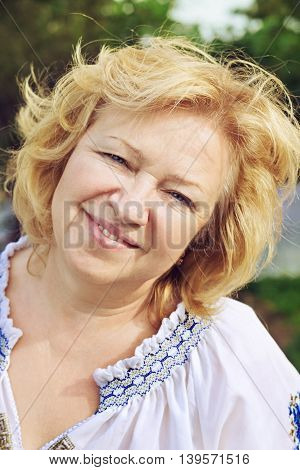 Lovely middle aged woman with smile looking at the camera outdoors.