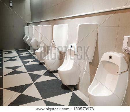 Men's room toilet urinal multiple, line of white porcelain urinals in public toilets