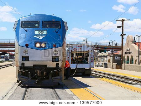 ALBUQUERQUE, USA - MAY 24, 2015: Engine of the Amtrak passenger train Southwest Chief seen from the front at the station. A tanker is parked on the platform next to the train and a worker is fueling the engine.