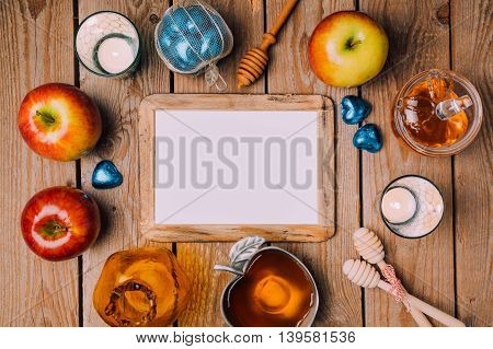 Jewish holiday Rosh Hashana poster mock up template with honey and apples on wooden table. View from above. Flat lay