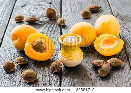 Essential oil from apricot kernels in a small yellow clay jar fresh apricots and apricot seeds on a dark wooden table