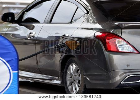 Fill the gas tank ,Gas pump nozzle in the fuel tank of a bronze car, refuel