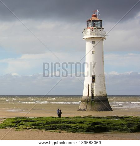 NEW BRIGHTON, ENGLAND, JUNE 29. The Perch Rock Lighthouse on June 29, 2016, in New Brighton, England. A couple watches the tide roll in at the Perch Rock Lighthouse in New Brighton Merseyside England
