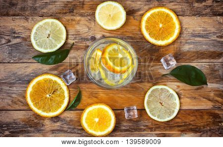 glass homemade lemonade orange lemon stands on an old rustic wooden table top view