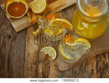 pitcher and glass homemade lemonade orange lemon stands on an old rustic wooden table