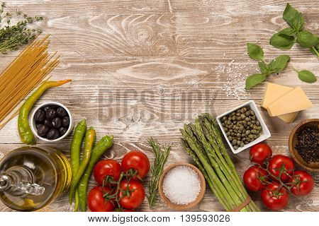 Thyme, spaghetti, olives, olive oil, tomatoes, salt, asparagus, capers, parmesan, cheddar cheese, fresh basil, organic ingredients on wooden surafce with copy space