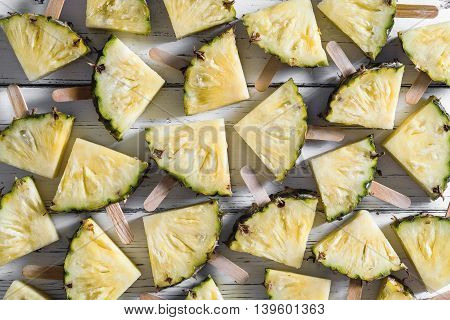 Pineapple slice popsicles on a white rustic wood background Popular summer fruit with yummy pineapple on a stick Flat lay photography of pineapple slice popsicles