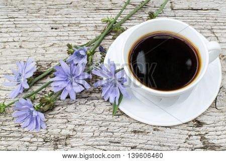 Medicinal plant chicory. The roots of the plants are used as a substitute for coffee. Drink from chicory in a cup on the old wooden background