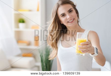 Rise your mood. Close up of glass of juice in hands of cheerful delighted woman holding it and smiling while going to drink it