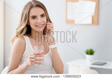 Modern way of life. Pleasant cheerful charming woman talking on cell phone and drinking water while expressing joy