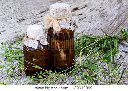 Medicinal plant shepherd's purse (Capsella bursa-pastoris) and brown pharmaceutical bottle on old wooden table. Used in herbal medicine healthy eating as well as for cosmetics purposes