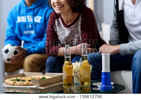 We believe in victory of our team. Close up of two bottles of beer standing on table next to pizza, popcorn with three football fans in background sitting on couch