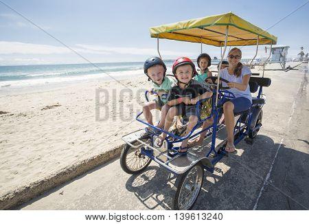 Family on a surrey bike ride along the coast of California