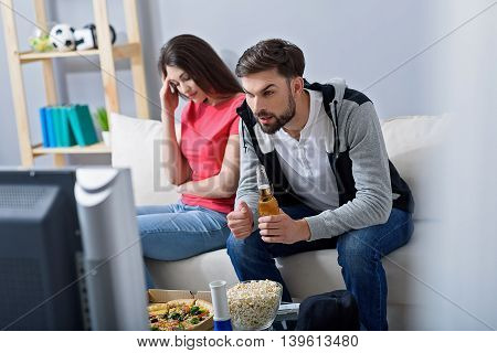 Enjoying interesting match. Man holding beer and watching football with his bored girlfriend sitting on sofa in background