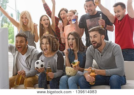 Finally we have got first goal. Group of happy friends rooting for their soccer team on TV and celebrating goal