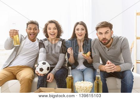 Our team most powerful. Group of smiling friends watching football match on tv on couch with window in background