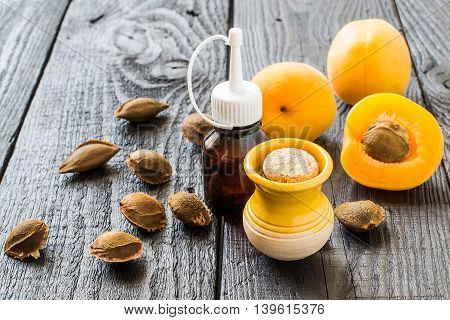 Essential oil from apricot kernels in small brown bottles and small yellow clay jar fresh apricots and apricot seeds on a dark wooden table