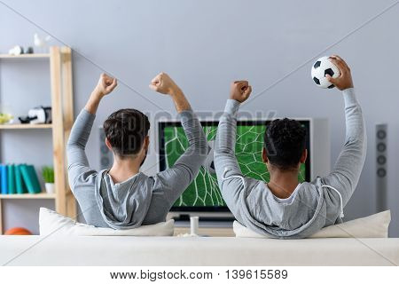 Without missing any games. Rear view shot of two men sitting on couch watching TV and cheering match of their favorite team