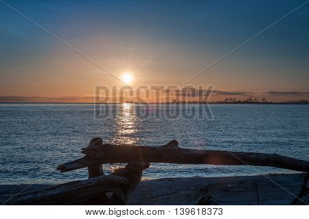 sunset over driftwood at twilight in Point Roberts Washington state USA