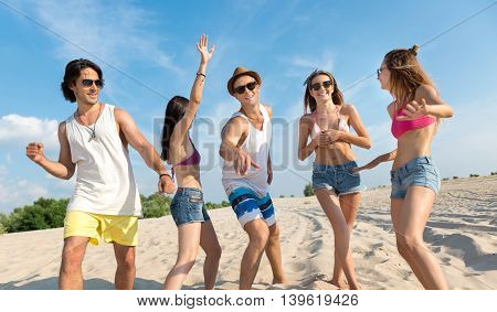 Just dance. Cheerful smiling reckless friends standing on the beach and having fun while expressing gladness