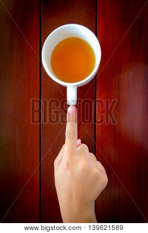 Hand with cup of tea on wood tabletop view