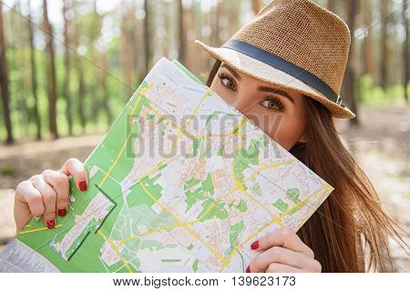 Carefree female tourist is looking for place of destination. She is standing and holding map near face. Woman is looking at camera with joy
