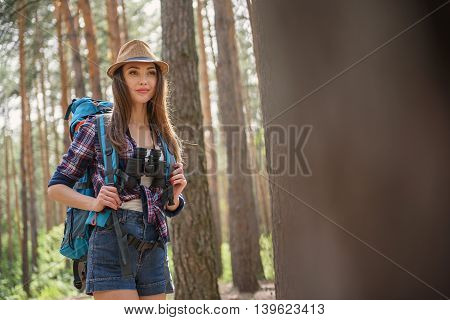 Cheerful female tourist is hiking in forest with joy. She is carrying backpack and binoculars