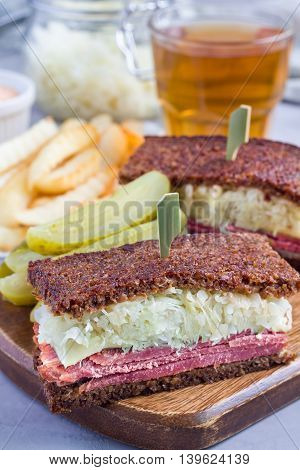 Classic reuben sandwich with corned beef swiss cheese sauerkraut and thousand island dressing on pumpernickel bread served with dill pickle spear and potato chips vertical