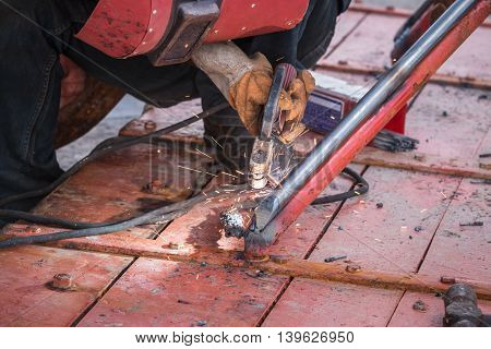 Man Welding Steel On The Part Of Fishing Boat At The Harbor