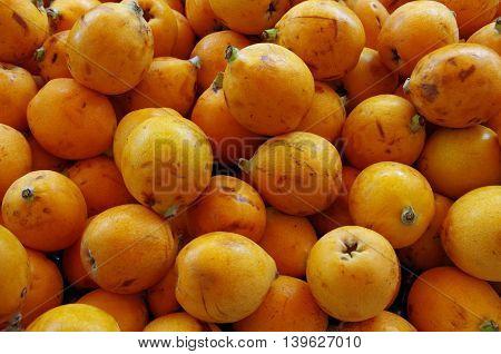 Asian orange loquat fruits piled for market close-up