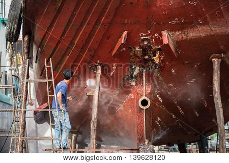 Man Working On Pressure Washer To Cleaning Boat Hull Barnacles Antifouling And Seaweed At The Harbor