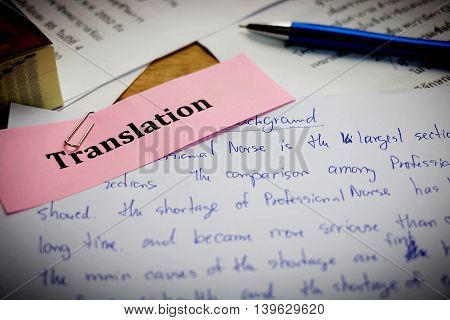 handwriting blue english words on white paper represent translating to English language