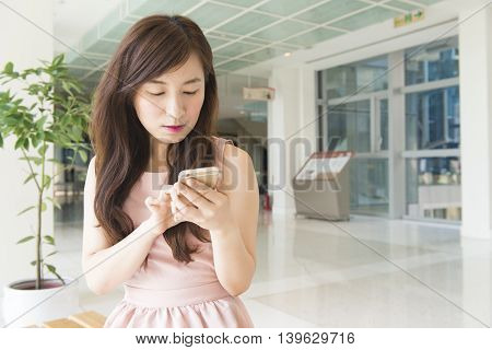 Woman sending message with smartphone in shopping mall