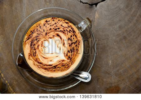 A Cup Of Coffee With Heart Pattern On Wooden Background Under The Morning Sunlight