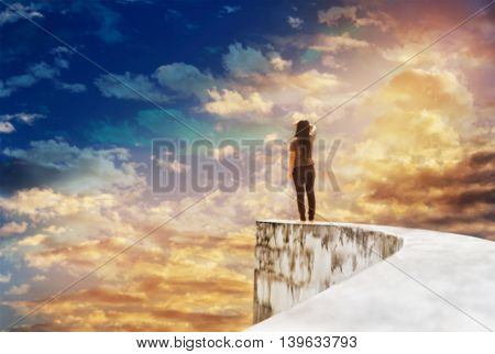 Blurred background backside or rare view of women or girl on dead end high way footpath or top of wall on mystery cloudy vast and extensive sky with dreamy and fancy mood women look up at worldwide