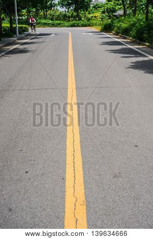 blacktop with double yellow lines divider under sunshine an unrecognizable lady riding a bicycle coming