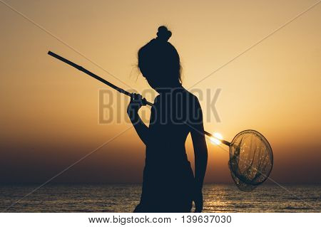 silhouette of a girl with a butterfly net on a background of sea sunset
