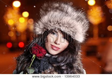Woman in night city holding red rose. Valentine's day concept