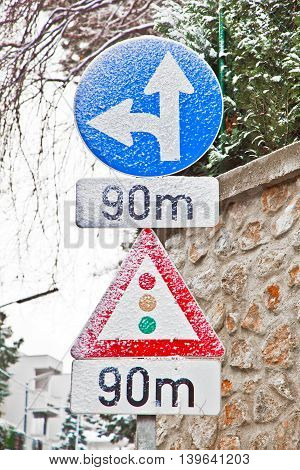 Traffic Sign Covered With Snow Indicates Traffic Light In 90 Meters