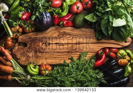 Fresh raw vegetable ingredients for healthy cooking or salad making with rustic olive wood board in center top view copy space. Diet or vegetarian food concept horizontal composition