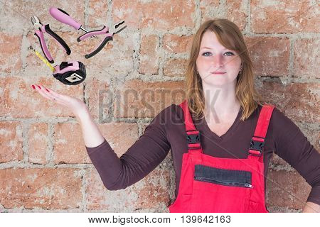 Young woman dressed in red overall is standing in front of an old brick wall. Woman is looking at the camera. Beyond her outstretched palm hand are DIY tools in the space.