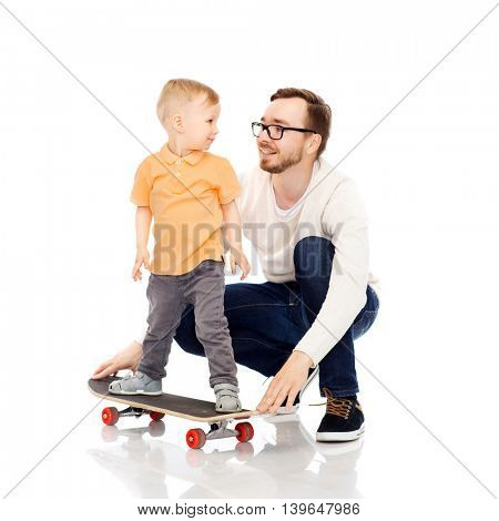 family, childhood, fatherhood, leisure and people concept - happy father teaching little son to ride on skateboard