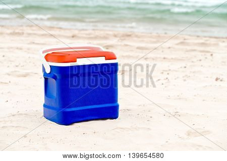 Cooler box in Australian Flag colors standing on sand at the beach