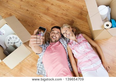 new home, technology, people, repair and moving concept - happy couple taking selfie with smartphone and lying on floor among cardboard boxes at home