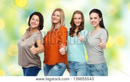 friendship, fashion, body positive, gesture and people concept - group of happy different size women in casual clothes showing thumbs up over green holidays lights background