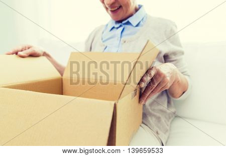 age, delivery, mail, shipping and people concept - close up of happy smiling senior woman looking into open parcel box at home